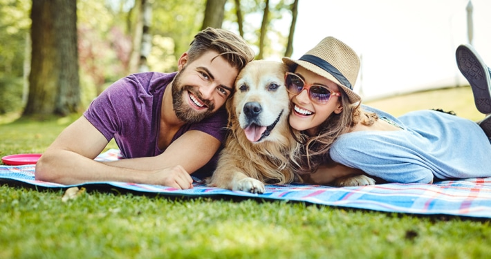 couple outdoors with their dog